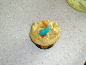 White cupcake with faux sandy mud topping and gummy worm.