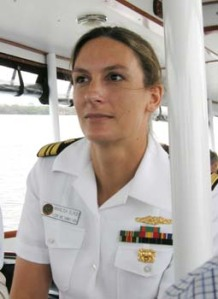 Lieutenent Commander Marilisa Elrod, a presumably white woman in a White Navy uniform appears to be driving a passenger boat.