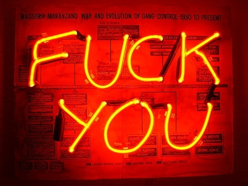 "Image of a neon sign, with yellowish orange letters spelling out ""FUCK YOU"" agains what appears to be a newspapered background."