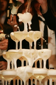 Tuxedo clad figures pour champagne into the top of a stacked pyramid of champagne flutes, creating a bubbling fountain.