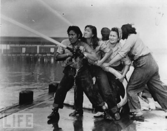 Women fight a fire during the Japanese attack on Pearl Harbor, 07 December, 1941. They are of various race and ethnicity, including presumably Hawai'ian, various Asian, and possibly one white and one black woman.