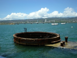 A gun turret of the USS Arizona sits just above the surface of the water, with Ford Island in the background