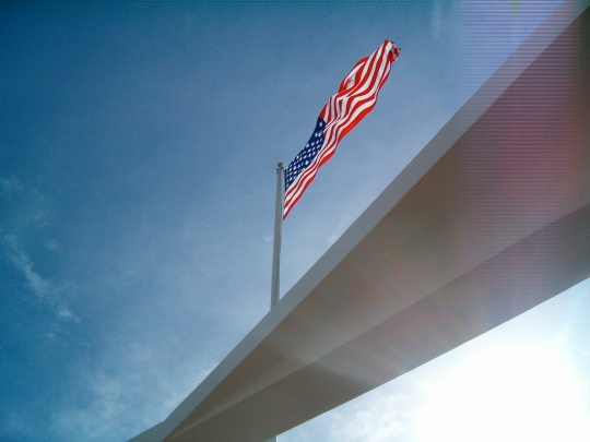 A view of the U.S. Flag from the underside, as taken from the center of the Arizona Memorial, Hawai'i, against a bright blue sky and bright sunlight.