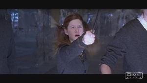 Ginny Weasley points her wand off screen.