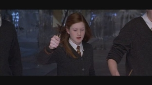 Ginny holds her wand and looks at the floor, off screen.