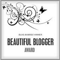 "A square black and white award with swirly bits and butterflies at the top. Text reads ""Blog Award Winner (next line) Beautiful Blogger (next line) Award"