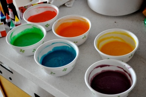 Six white bowls with four-leaf clover pattern, each containing one colour; red, orange, yellow, green, blue and violet on a white counter top.