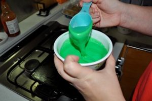 Bright green pancake batter in a white bowl being scooped by pale hands holding a blue measuring cup.