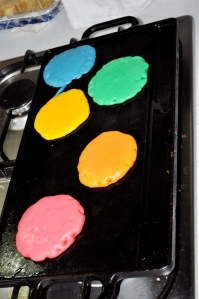 Five pancakes, one of each color, red, orange, yellow, green, blue, cook on a stove-top griddle.