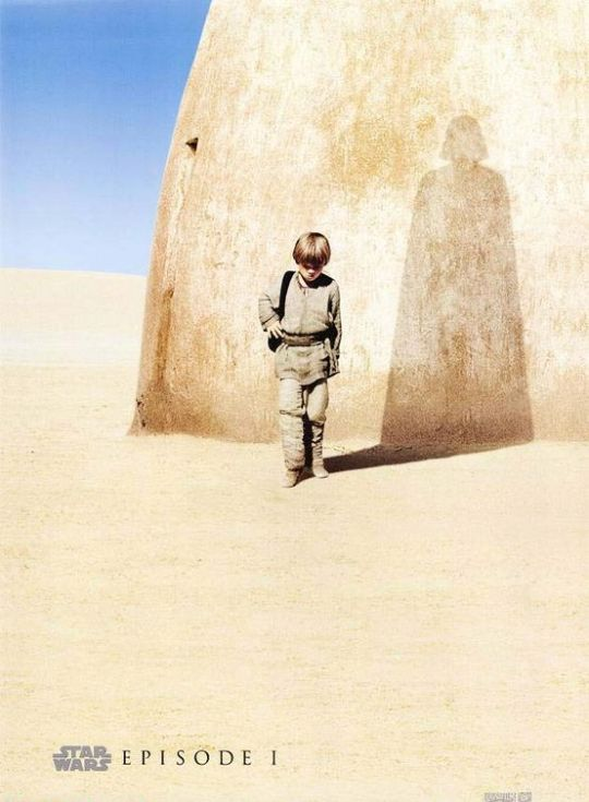 Movie Poster From Star Wars Episode I -- The Phantom Menace: a boy walks, head down carrying a knapsack in a desert like landscape with a stark blue sky near a sand-like structured wall. The sun cast his shadow on the wall, which is the shape of a tall, cloaked and helmeted man, believably Darth Vader.