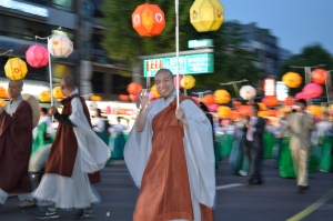This blurry picture is my favorite. The monks are so cheerful and friendly. Every time I meet one I smile and giggle, I swear. A Monk in loose orange and white garments carrying lanterns smiles and waves.