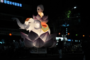 "A small child-Buddha sits in a lotus blossom atop a baby elephant inside another lotus blossom, which is all a lantern lit and pulled by shadowy figure along a lit street in South Korea. The base says ""Buddha's Birthday"" in English and Han-gul (Korean)"