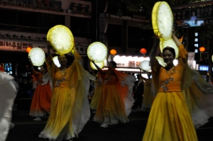 Women in yellow, orange and white dresses dance in the night street with moon-shaped lanterns for the Buddha's Birthday parade. They smiled for my camera!