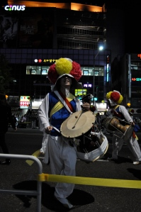 A Korean drummer, dressed in a uniform with a fluffy red and yellow had, a blue shirt with white long sleeves and a yellow sash, and white pants and shoes, with a traditional drum, stops for my camera after running through the streets.