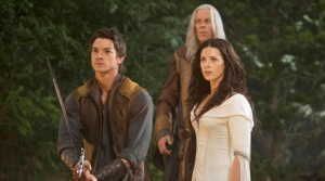 Three presumably white actors: a young man in a loose blue shirt and vest with a sword, a woman with long dark hair in a flowing white robe, and a very tall old man in a tan/orange shirt stand in the woods.