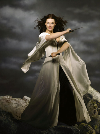 Bridget Regan, a pale woman with a mass of thick, dark hair, dresses as Kahlan Amnell, the Mother Confessor from <em>Legend of the Seeker</em> and <em>The Sword of Truth Series</em> by Terry Goodkind. She wears a long, white, flowing dress, and weilds two daggers, standing at the edge of a cliff against a stormy looking sky.