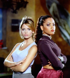 "a pale woman with blonde hair in a grey tank to with her arms cross across her midd, and a darker complexioned woman with black hair in a purple long-sleeved shirt in the same pose stand back to back. The both have their ""serious business"" faces on. They are Sara Michelle-Gellar as Buffy the Vampire Slayer and Bianca Lawson as Kendra the Vampire Slayer."