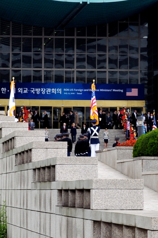 An extremely cropped photograph of the National War Museum of Korea's front steps and main doors, with various Republic of Korea military standing at attention, and in the center, the very tiny figures of Secretary of State Hillary Clinton, and Secretary of Defense Bob Gates, and Defense Minister Kim Tae-Young are walking down the stairs.