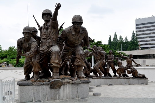 A statue of South Korean soldiers poised as if fighting curved in the frame from front left back to right, ending in a line of what looks to be Korean civilins suffering from the strife of war.