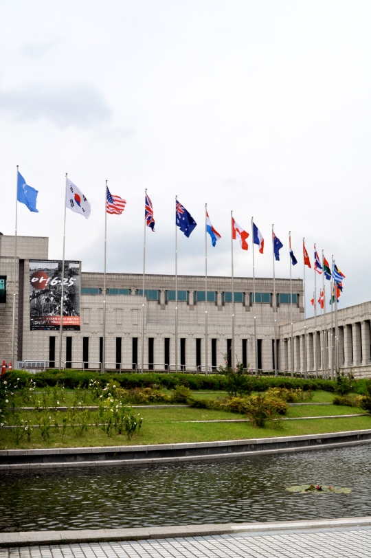 Exterior of the Korean War Museum, showing a pond with small fountains, a manicured lawn, and many flags of the various nations that came to the aid of South Korea during the Korean war next to the flag of South Korea in a wide semi-circle starting from the front left and arching around to the back right.