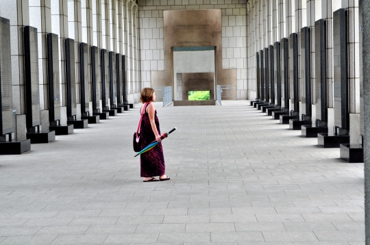 A pale Native American girl with short-cropped hair in a long purple and black maxi-style dress with a messenger bag slung over her shoulder and an umbrella in her hand pauses to look at the wall of names carved with names of those who gave their lives during the Korean war in a long hall of columns.