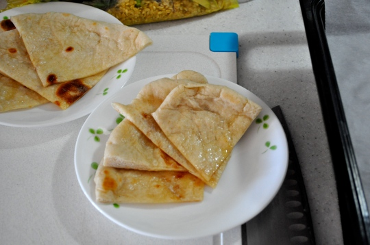 Wedges of naan, an Indian flatbread, sit on plates on a cutting board.