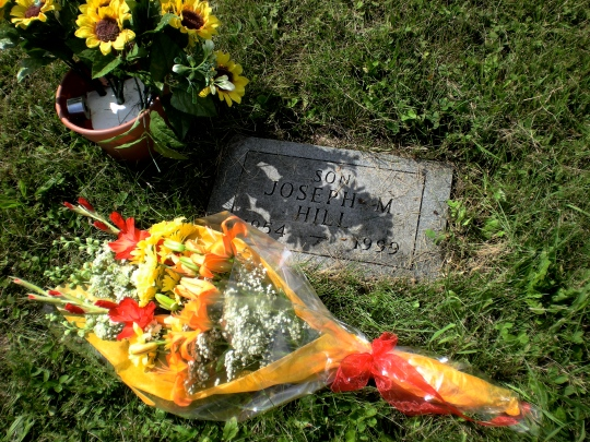 """a very small grave marker, says """"Son, Joseph M. Hill"""" with the years of life, and a boquet of bright flowers are next to it."""