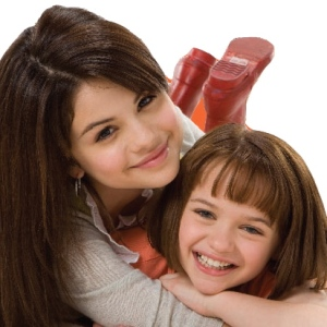 Promo-still of Selena Gomez, a latina young woman, and Joey King, a pale girl, caught in a sisterly embrace lying on their stomachs as Beezus and Ramona Quimby for the movie Ramona and Beezus.