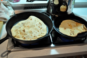 Two cast iron skillets on a small stove top with rounds of naan (flat bread) cooking in them).