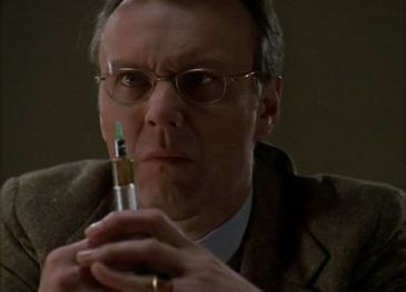 Anthony Stewart Head, as Rupert Giles, a pale British man in a suit, holding a syringe in front of his bespectacled face.