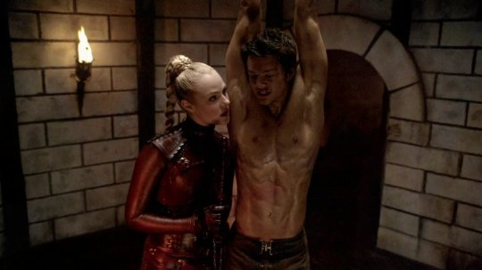 "Jessica Marais as ""Denna"" the Mord-Sith, and Craig Horner as Richard Cypher, the Seeker in <em>Legend of the Seeker</em>. Richard is shackled and hanging from the ceiling with no shirt, sweat and blood all over him, as Denna, clad in blood-red leather and a single blonde braid holds a thin rod up against him as she leans close with a threatening look on her face. She is torturing him."