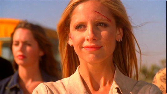 Sarah Michelle Gellar as Buffy Summers, a pale woman with blonde hair. She looks on with the beginning of a smile, as if a great weight has been lifted. A pale brunette woman (Eliza Dushku as Faith) is blurred in the background.