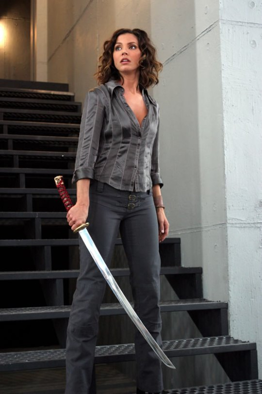 Cordelia Chase, as portrayed by Charisma Carpenter, a pale woman with dark brown hair, standing on stairs holding a long, slightly curved sword.