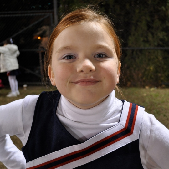 A pale native american girl with dyed red hair and blue-grey eyes. She is wearing a white turtle-neck shirt under a red, white, and blue cheerleading uniform. She is smiling.